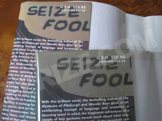 "The front flap of the first issue dustjacket says ""SEIZE FOOL"" in a gray speech bubble."
