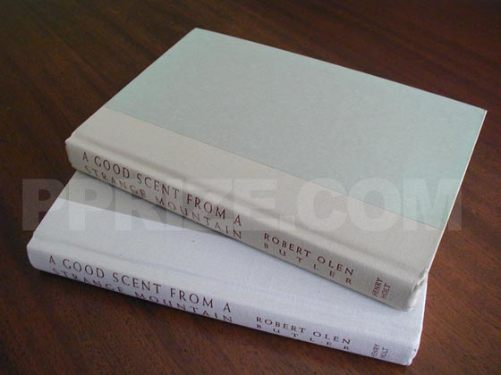 The book on the top is a first printing.  It has light green boards with beige cloth