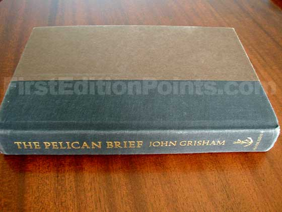 The Pelican Brief first edition boards are brown with a black spine, and gold le