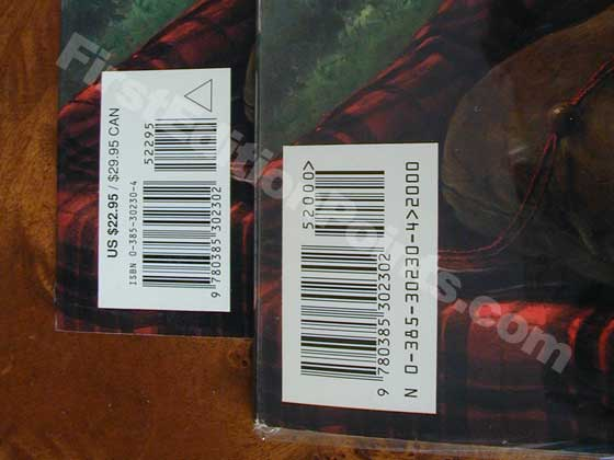 "The first issue dust jacket (right) has ""52000"" over the smaller bar code, while later"